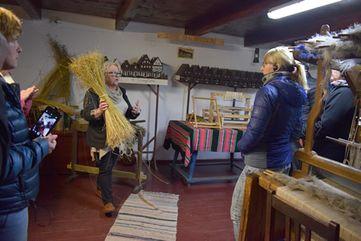 in einem Museum zeigt eine Frau mit Folklorebekleidung eine Garbe mit getrockneten Leinen hoch