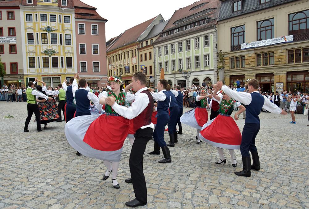 Tanzpaare in Folklorekostümen tanzen auf einem Platzz