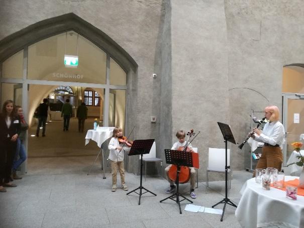 3 osoby grają na instrumentach na podwórku